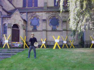 Aktivist*innen markieren symbolisch die Kirche in Immerath als Ort, der abgebaggert werden soll mit gelben Xen. Vor Ort wird auch Theatherstück aufgeführt.